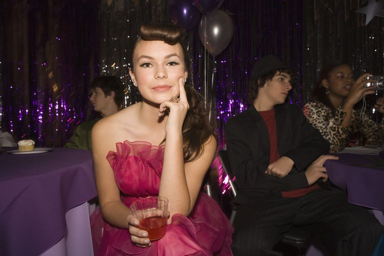 Pensive teenage girl sitting at prom