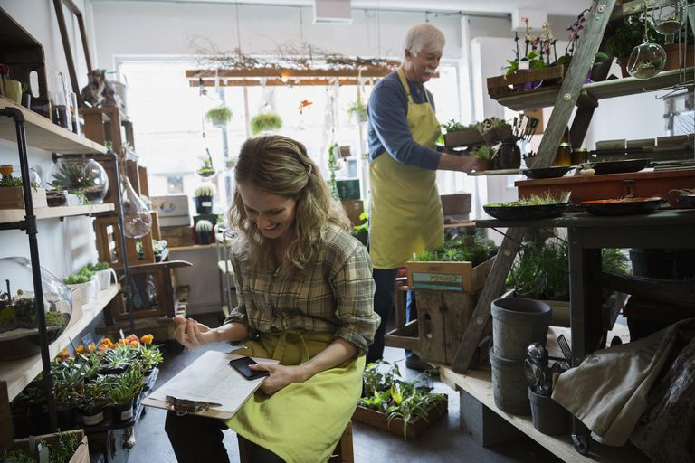 Terrarium shop owner taking inventory with clipboard