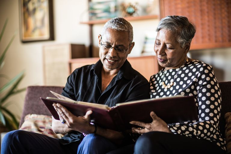 Senior couple (60yrs) looking at photo album on couch at home