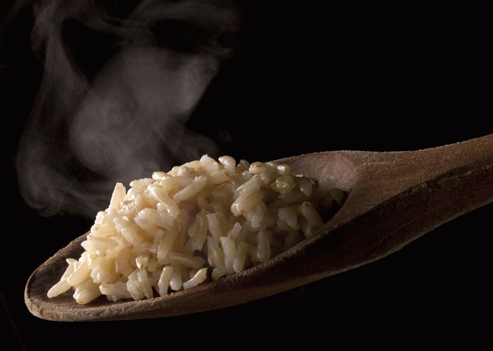 Basmati rice on a wooden spoon with steam
