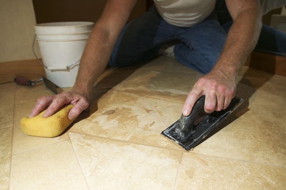 Hands of marble mason scraping floor