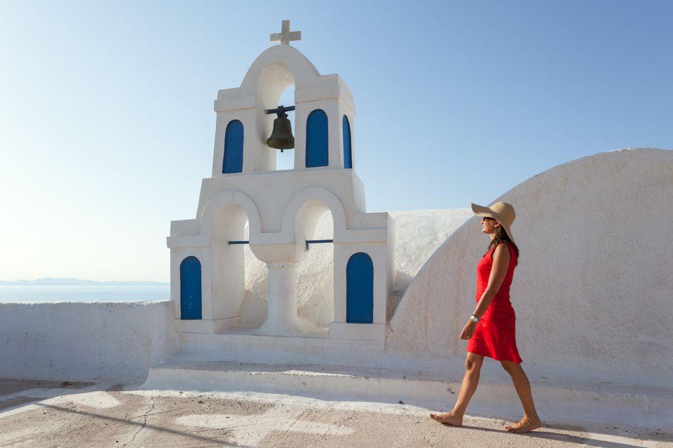 Woman in red walking in greek town, Santorini