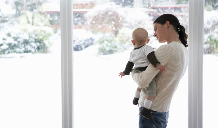 woman holding baby looking out window at snow