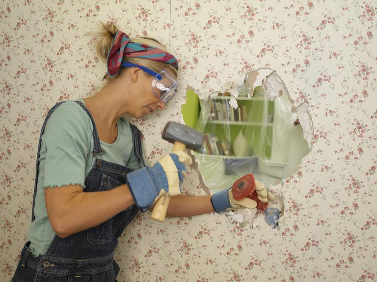 Young woman knocking hole through wall using hammer and chisel