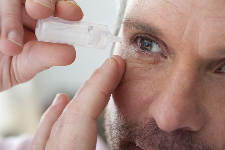 Mature man applying eye drops into eye