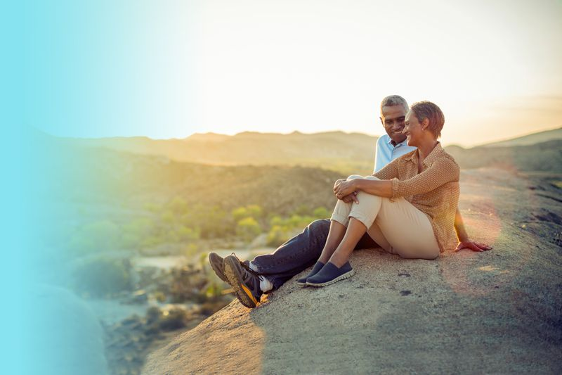 couple sitting on rock at sunset