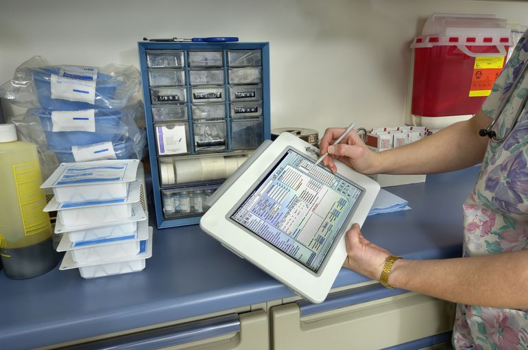Nurse holding electronic unichart entering patient record, close-up