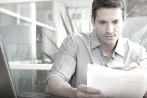 Adult man looking over papers