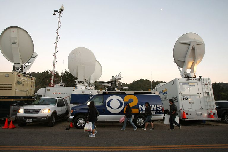 A photo of live microwave and satellite news trucks on the scene of a story.