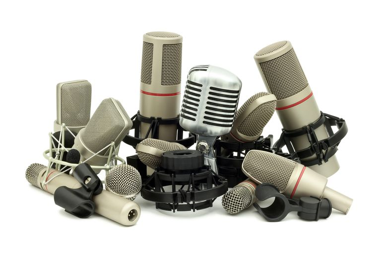 A pile of studio microphones, isolated on a white background