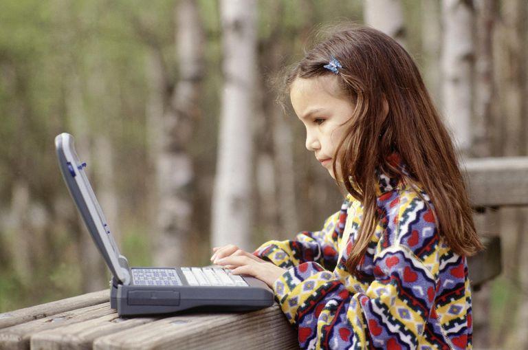 Girl using laptop outdoors, AK