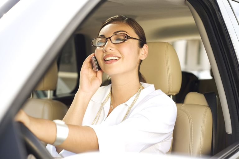 Woman in car talking on cell phone.