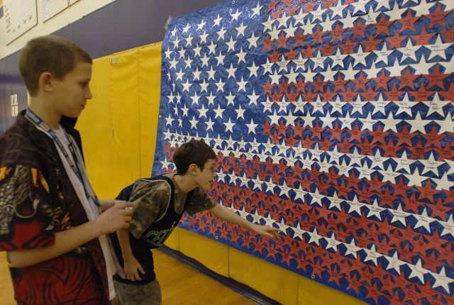 Middle School students examining veterans' names on a flag