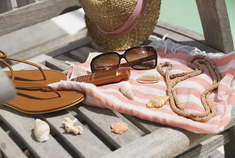 CClose-up of suntan lotion and sunglasses on beach chair with sun hat and flip-flops