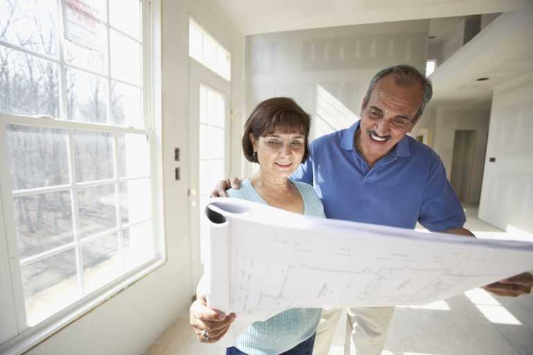 Retired couple looking at home blueprints after qualifying for a mortgage.