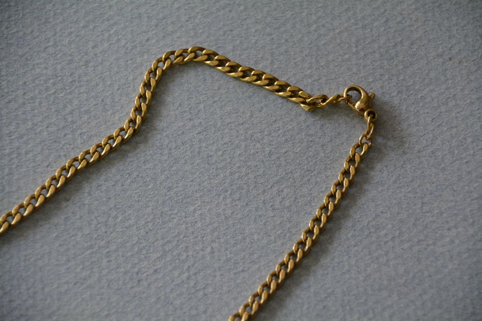 High Angle View Of Gold Chain On White Paper