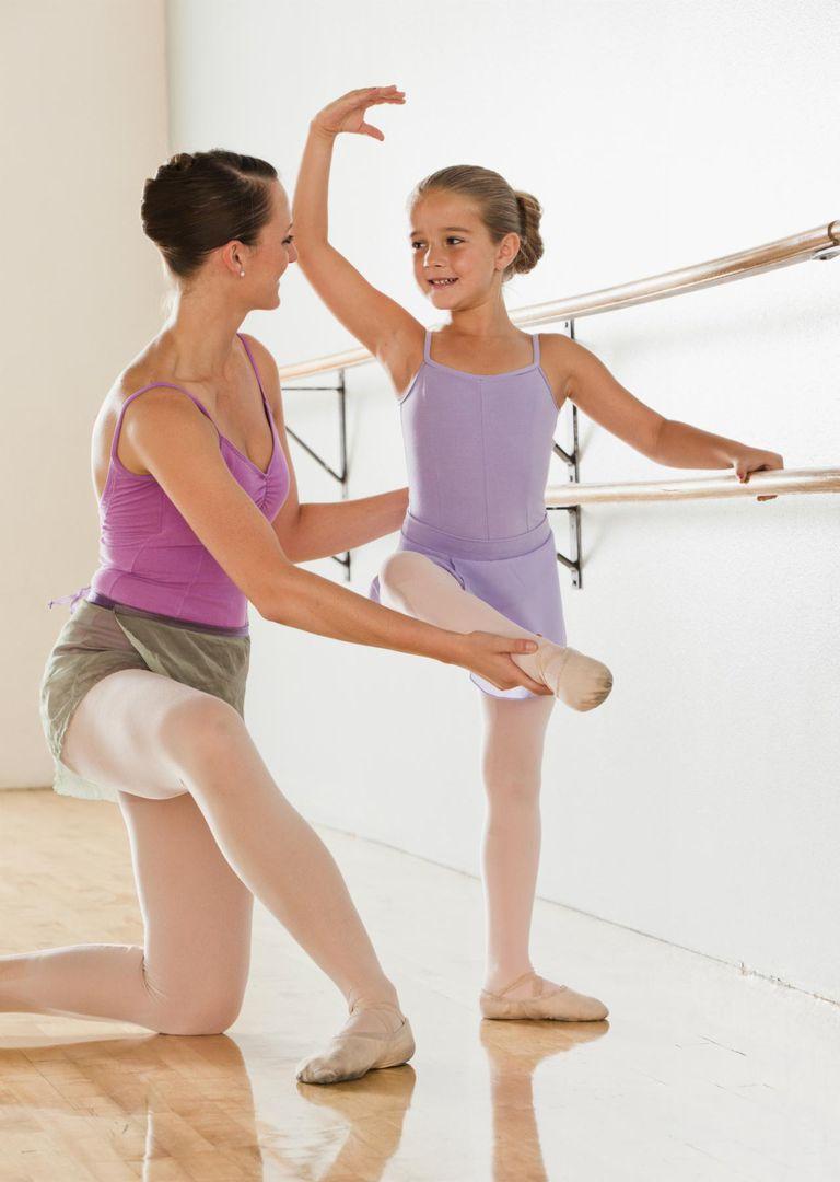 Female instructor training ballet dancer (6-7) in dance studio