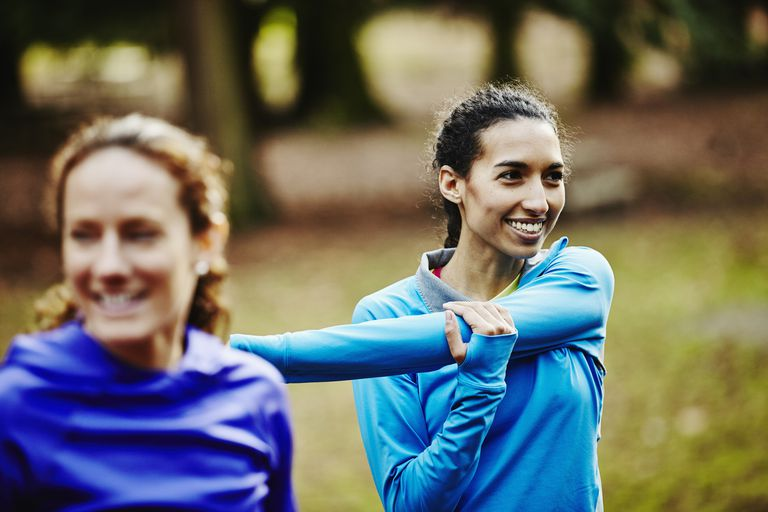 Smiling female runner stretching with friends