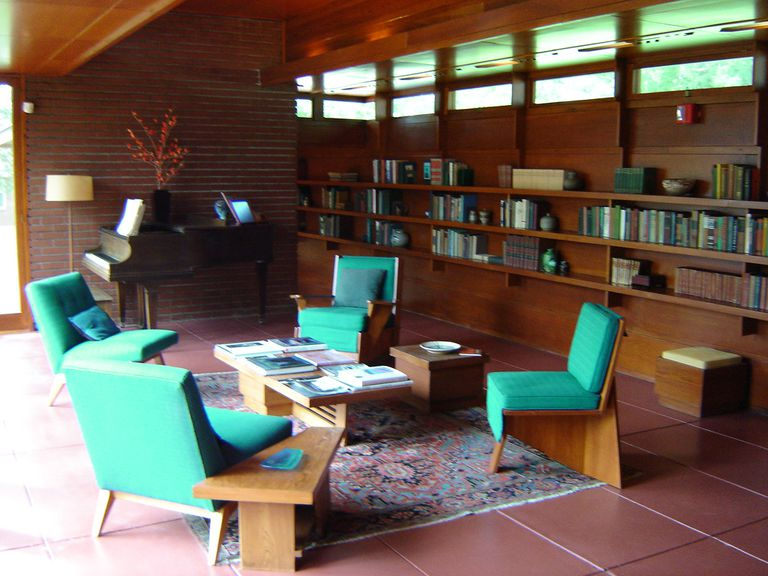 Turquoise chairs around a coffee table, nearby built-in bookshelves and a  grand piano. Interior of Frank Lloyd Wright's ...