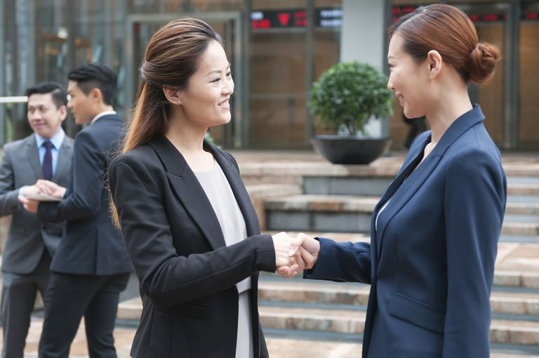Asian Businesswomen Shaking Hands in Financial District