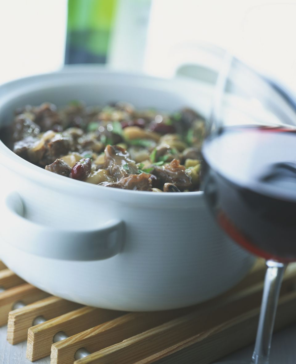 A glass of red rhone wine and a beef and bean casserole.