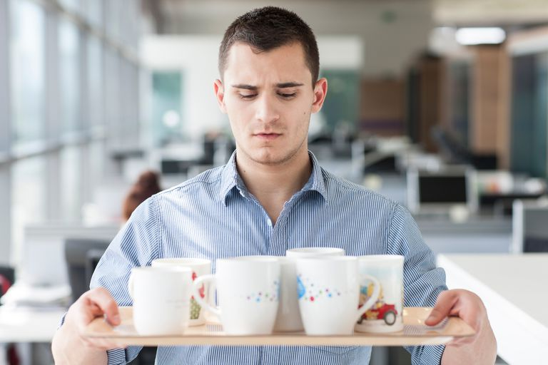 Nervous looking man carrying tray of mugs