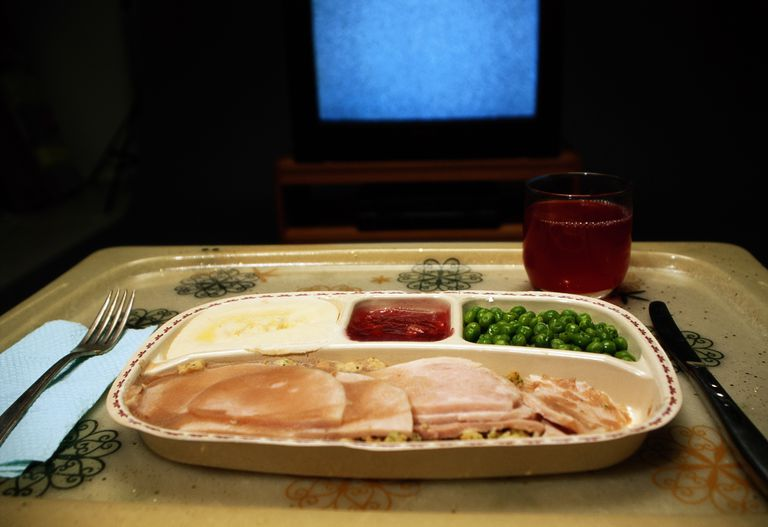 Turkey, mashed potatoes and peas dinner on tray in front of TV