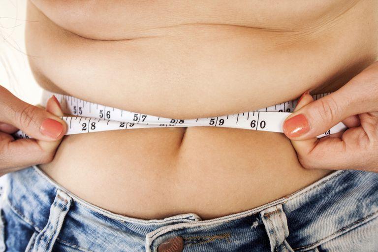 tape measure tighten around a girl's stomach