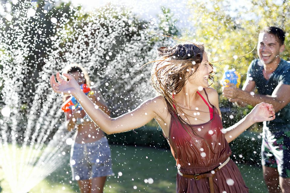 Woman running through a sprinkler