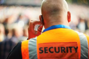 Rear view of a security guard listening to his headset