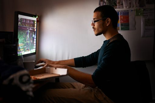 A man sits in the dark lit up by the game on his computer screen.