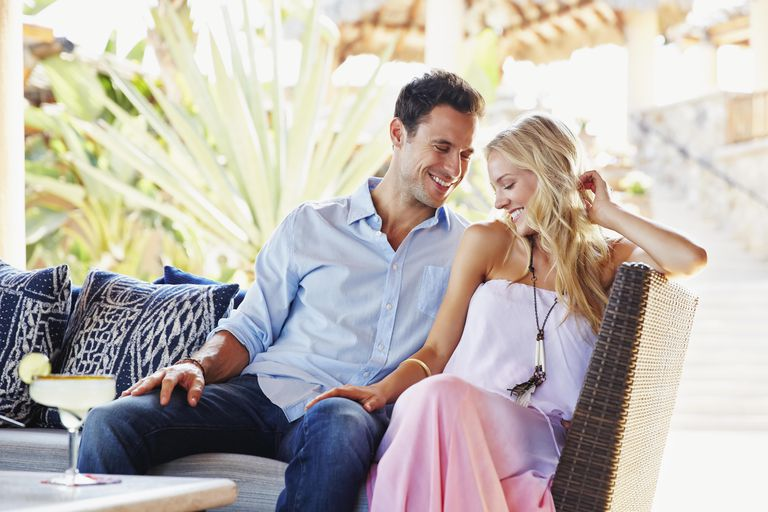 Couple having margarita together on sofa