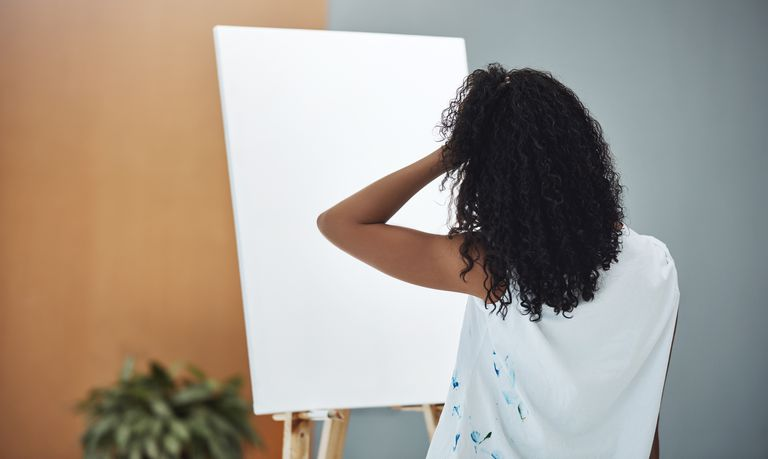 female painter looking at blank canvas