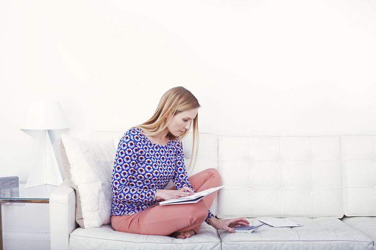 Woman doing bills on the sofa