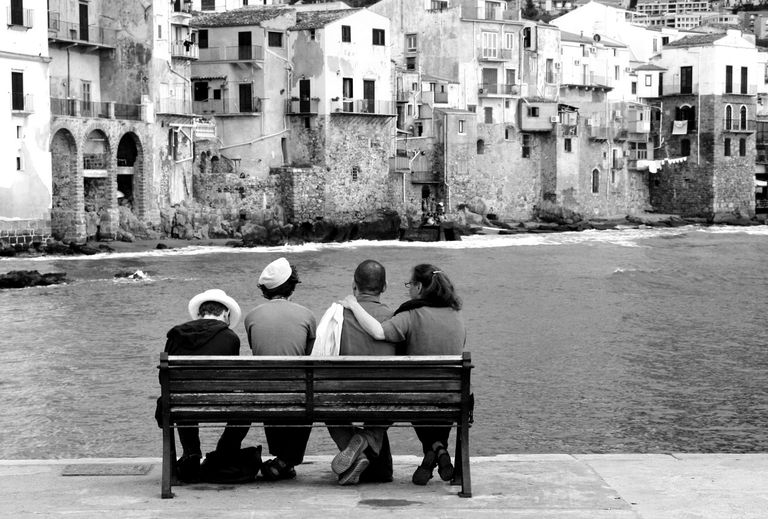 Sicilian family sitting on bench in Cefalu