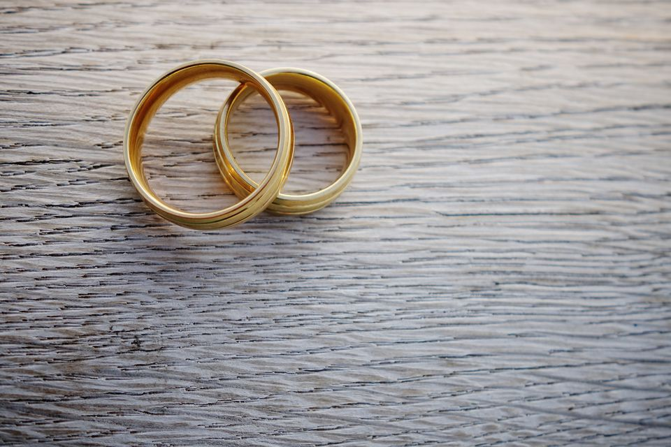 A pair of gold wedding rings on a wood-grain surface