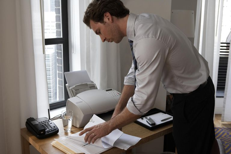 Young businessman looking at paperwork on desk by window
