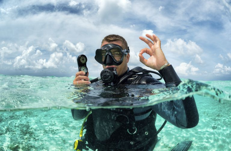 Scuba diver at the surface of a tropical dive site.