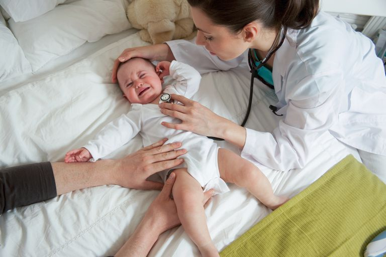 Doctor checking crying baby heartbeat on bed