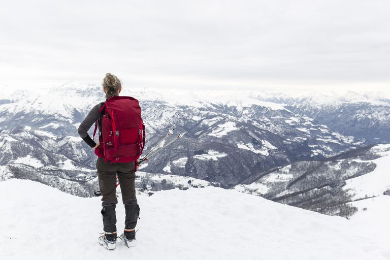 Woman hiker with rucksack on top mountain