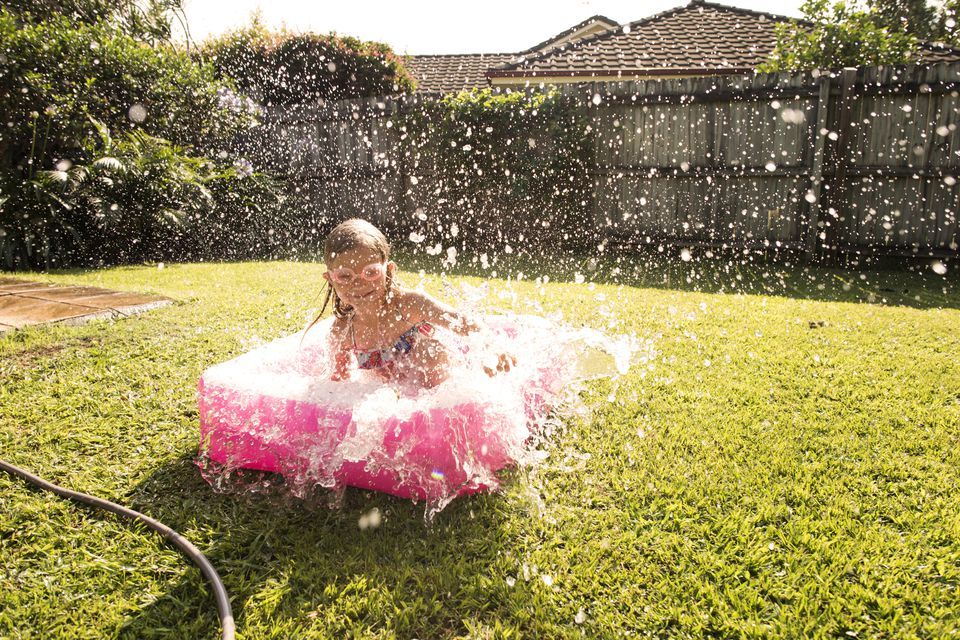 Girl playing in backyard pool