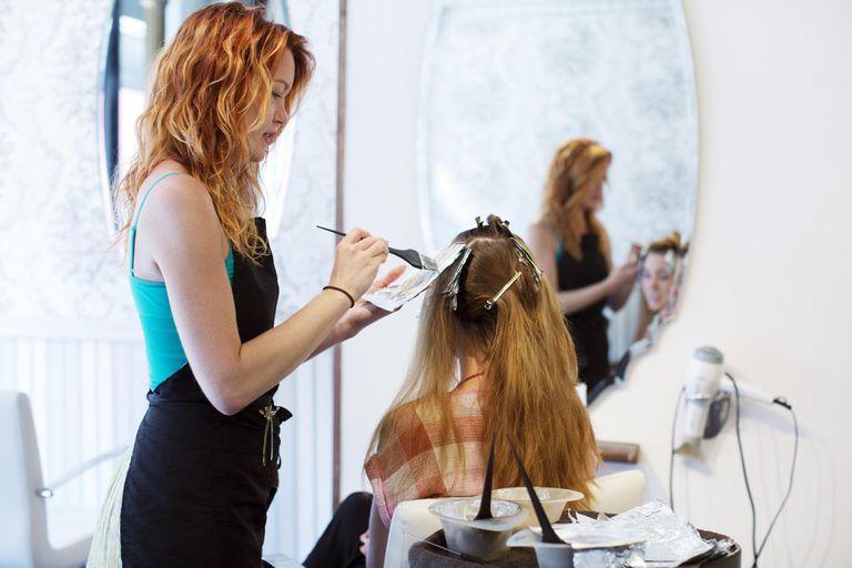 Hair Stylist Dying a Woman's Hair in Salon