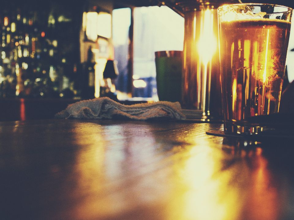 A pint of beer on a bar.