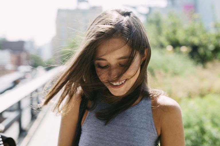 brunette with hair blowing over her face
