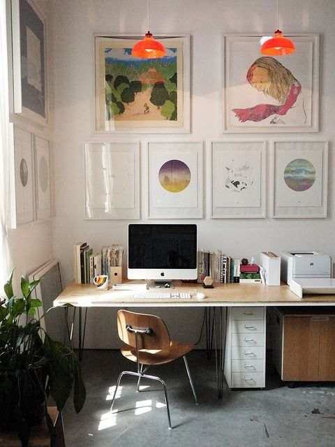 home office with gallery wall of colorful paintings