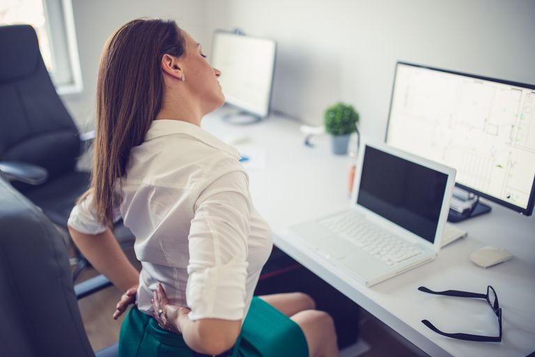 Woman sitting at her desk rubbing her back and stretching