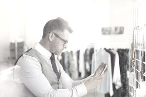 man taking photo of clothing items with phone
