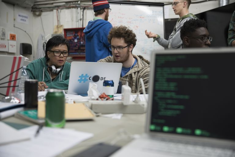 Team of hackers working hackathon at laptop in workshop