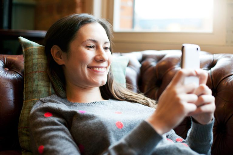 Woman lying on sofa using smartphone.