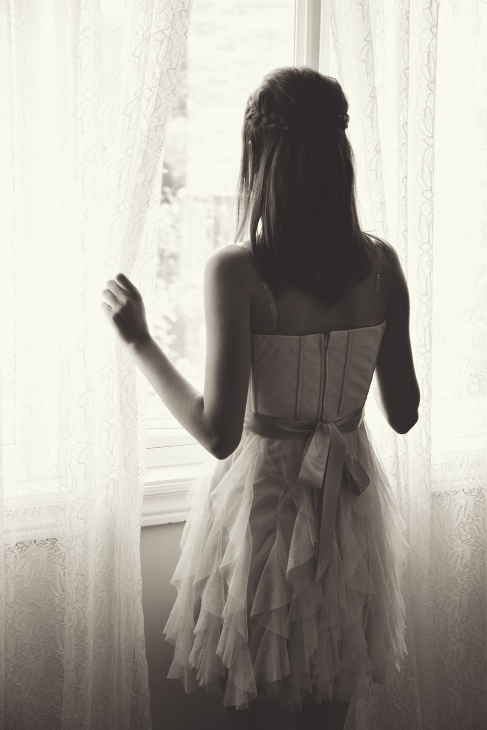 Teenage girl in graduation dress looking out of a window
